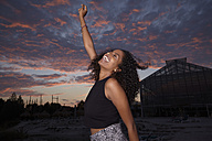 Happy young woman dancing at evening twilight - KD000506