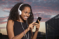 Portrait of excited young woman hearing music with headphones at evening twilight - KD000508