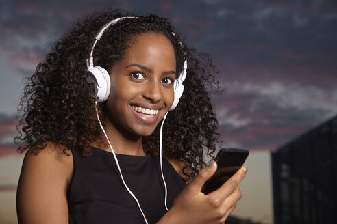 Portrait of excited young woman hearing music with headphones at evening twilight - KD000509