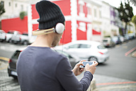 Young man with headphones and smartphone listening music - ZEF000030