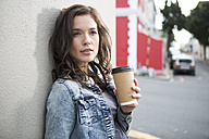 Portrait of young woman with coffee to go leaning at house front - ZEF000048