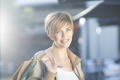 Portrait of smiling young woman with shopping bags - ZEF000105