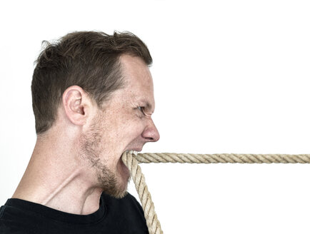 Mann pulling a rope by the teeth - MW000068