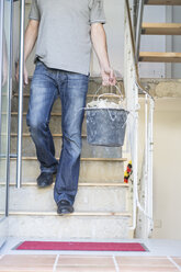 Man carrying bucket with rubble during house renovation - DRF001090