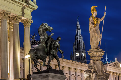 Austria, Vienna, view to parliament building, town hall tower and statue of goddess Pallas Athene by night - EJWF000535