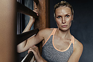 Serious woman at wallbars in gym - MFF001162