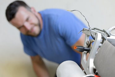 Young man examining enduro motorcycle - LAF001050