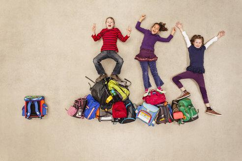Children cheering on pile of school bags - BAEF000776