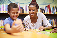 Young woman and boy doing a jigsaw puzzle in library - ZEF000759