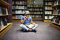 Boy with helmet and gun reading book in library - ZEF000195