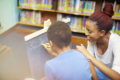 Young woman doing maths with boy in library - ZEF000199