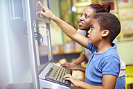 Young woman and boy using computer in library - ZEF000763