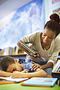 Young woman awaking sleeping boy in library - ZEF000210