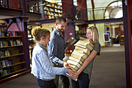 Female student carrying pile of books in a library assisted by friends - ZEF000134