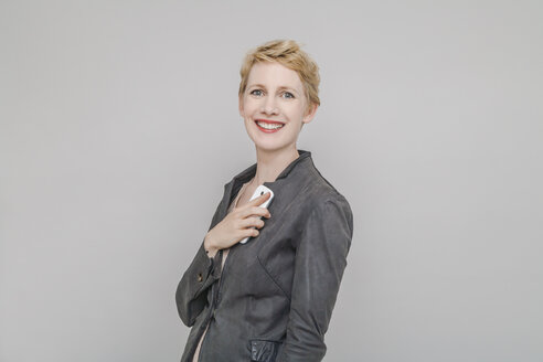 Portrait of smiling blond woman with smartphone in front of grey background - TCF004236