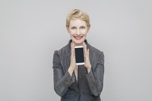 Portrait of smiling blond woman showing her smartphone in front of grey background - TCF004241