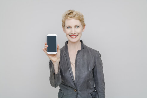 Portrait of smiling blond woman showing her smartphone in front of grey background - TCF004244