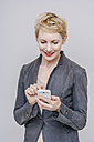 Smiling blond woman using her smartphone in front of grey background - TCF004248