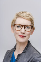 Portrait of smiling blond woman wearing glasses in front of grey background - TCF004267