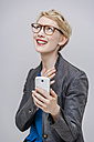 Portrait of smiling blond woman with her smartphone in front of grey background - TCF004273