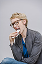 Portrait of blond woman biting her smartphone in front of grey background - TCF004276