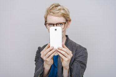 Blond woman taking a picture with her smartphone - TCF004281