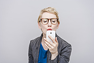 Blond woman pouting mouth taking a selfie with her smartphone - TCF004283
