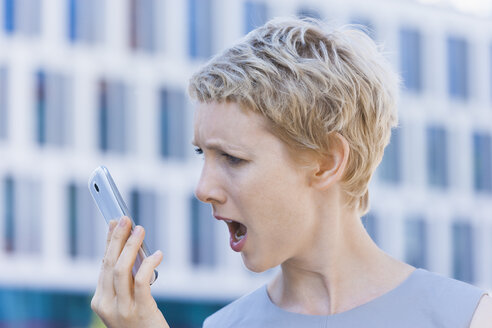 Angry blond woman shouting at her smartphone - TCF004297