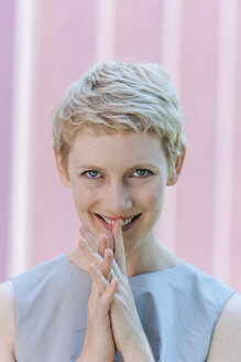 Portrait of smiling blond woman with finger on her mouth - TCF004299