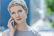 Portrait of blond woman telephoning with smartphone - TCF004307
