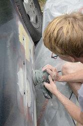 Germany, Zeuthen, Man mending car paint - BFRF000503