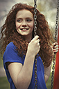 Portrait of smiling girl with curly red hair sitting on a swing - GDF000409