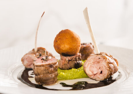 Haute Cuisine, Pork roulade, Spare ribs, Pea puree, Potato croquette and chocolate sauce on plate - KMF001411