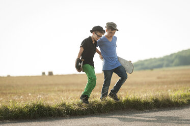 Two boys walking over a field with her skateboards - PAF000883