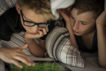 Two boys lying on bed using digital tablet - PAF000863