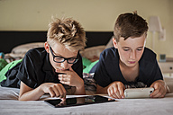 Two boys lying on bed using digital tablet - PAF000865