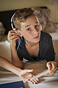 Portrait of a boy lying on bed hearing music with head phones - PAF000866