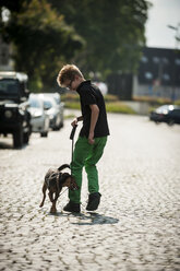 Boy walking with his dog along a street - PAF000879