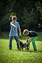Two boys playing on a meadow with their dog - PAF000867