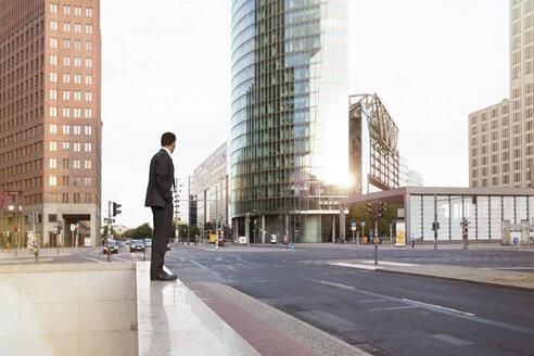 Germany, Berlin, Businessman standing on balustrade - FKF000609