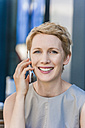 Portrait of smiling blond woman telephoning with smartphone - TCF004442