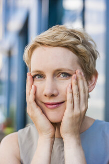 Portrait of smiling blond woman with hands on her face - TCF004444