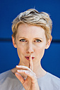 Portrait of blond woman with finger on her mouth in front of blue background - TCF004450