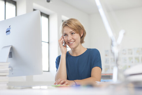 Portrait of smiling young woman telephoning at her desk in a creative office - RBF001834