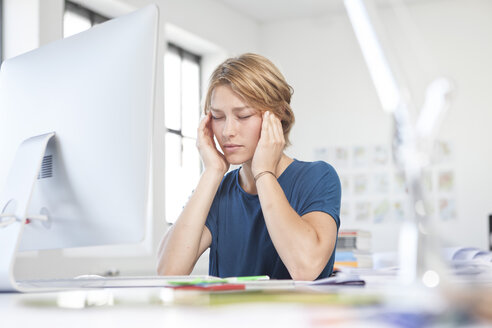 Portrait of young woman with headache at her desk in a creative office - RBF001808