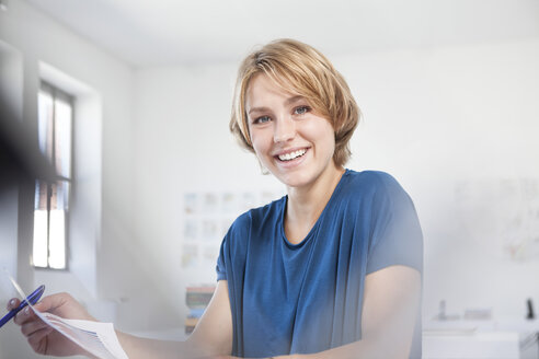 Portrait of smiling young woman at her desk in a creative office - RBF001840