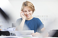 Portrait of smiling young woman telephoning at her desk in a creative office - RBF001843