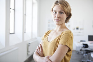 Portrait of young woman with crossed arms in a creative office - RBF001815