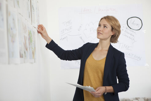 Portrait of young woman looking at wall with concepts in an office - RBF001849