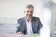 Portrait of smiling man at his desk in an office - RBF001859